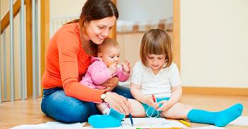 Mãe com dois filhos, bebé e menina a brincar