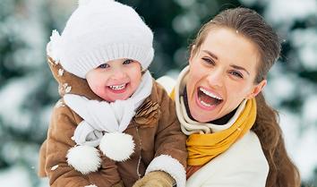 Mãe e filha com pele protegida na neve